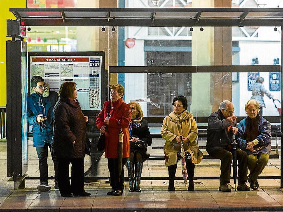 Usuarios del bus, esperando en una parada, en plena huelga.