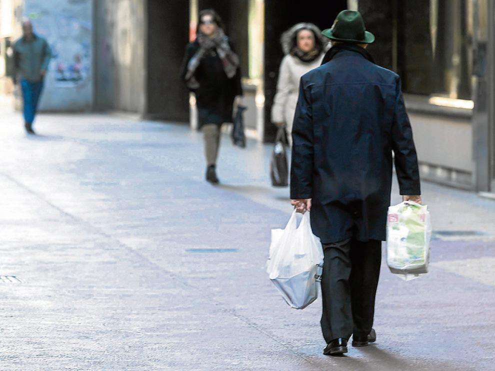 Un transeúnte pasea por Zaragoza con dos bolsas de plástico.