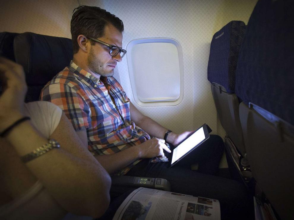 Un pasajero utilizando una tableta durante un viaje a bordo de un avión