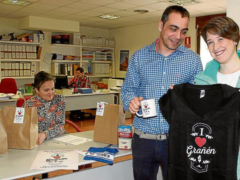 Marta Fiestas, junto al alcalde de Grañén, Carlos Sampériz, enseña la camiseta recibida al censarse.