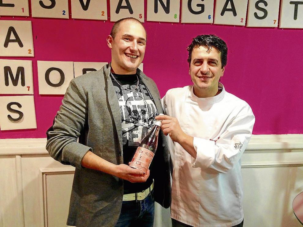 Los cocineros Carlos Martín y Roberto Baquero, con una botella de vino solidario de Care.