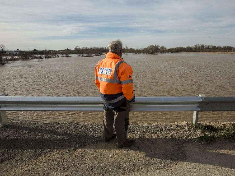 Situado sobre los nuevos aliviaderos abiertos en Novillas, un voluntario de Protección Civil observa el paso de la crecida del Ebro.