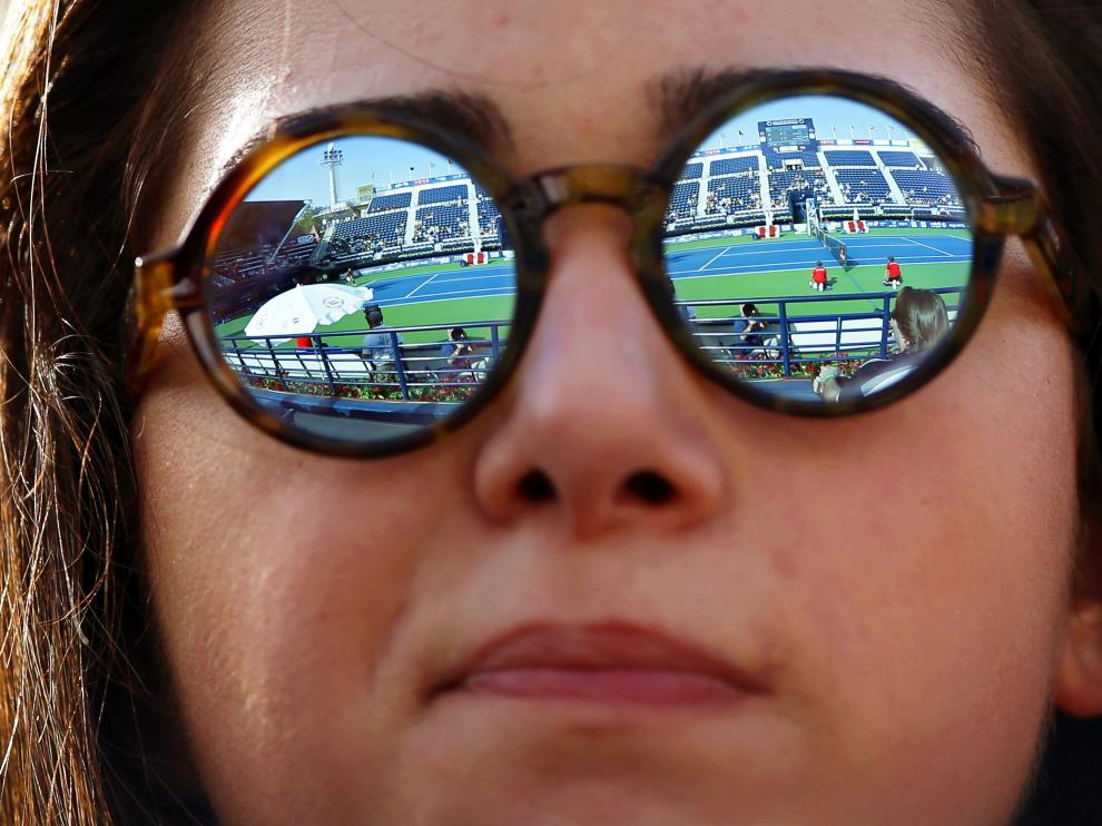 Una joven con gafas en un partido de tenis.
