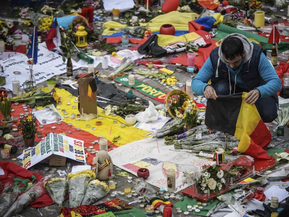 Un joven deposita una bandera de Bélgica junto a mensajes, flores y velas en homenaje a las víctimas.