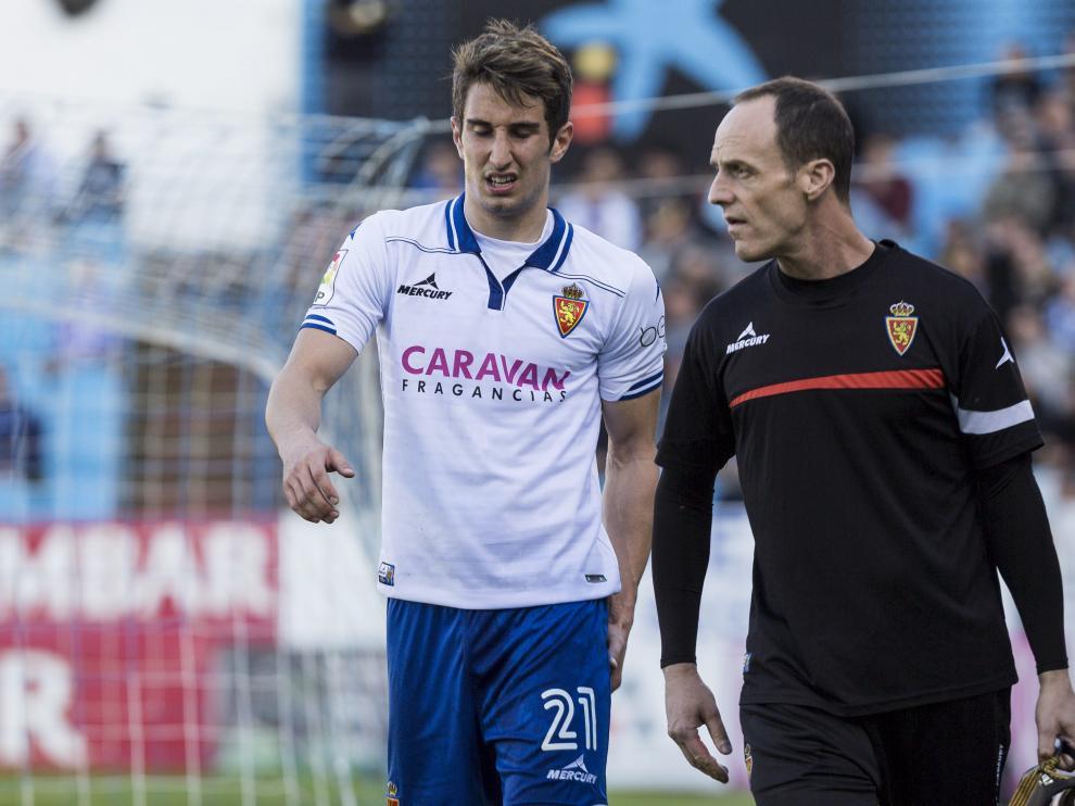 Momento en el que Joan Campins abandona el campo lesionado, acompañado del fisioterapeuta Míchel Román, en el partido ante el Girona del pasado domingo.