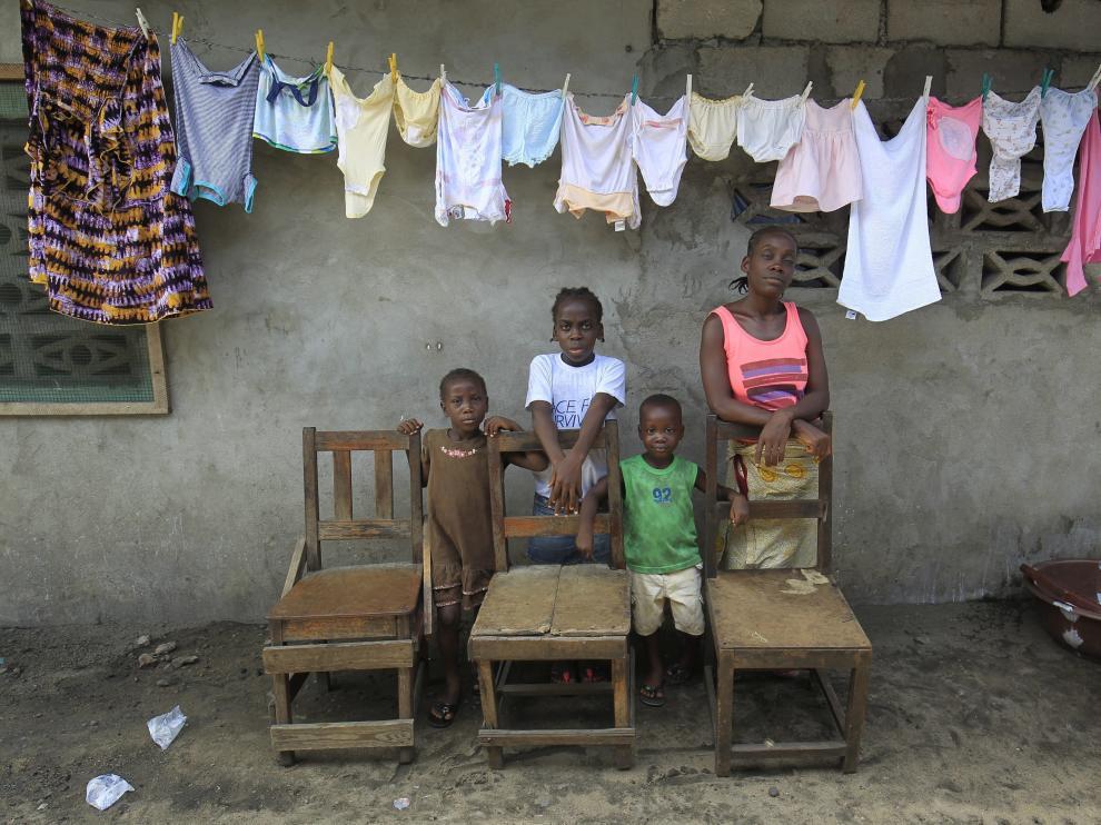 Victoria Topay (d) y sus hijos posan junto a sillas vacías que simbolizan a su marido y otros familiares fallecidos víctimas del ébola en Monrovia.