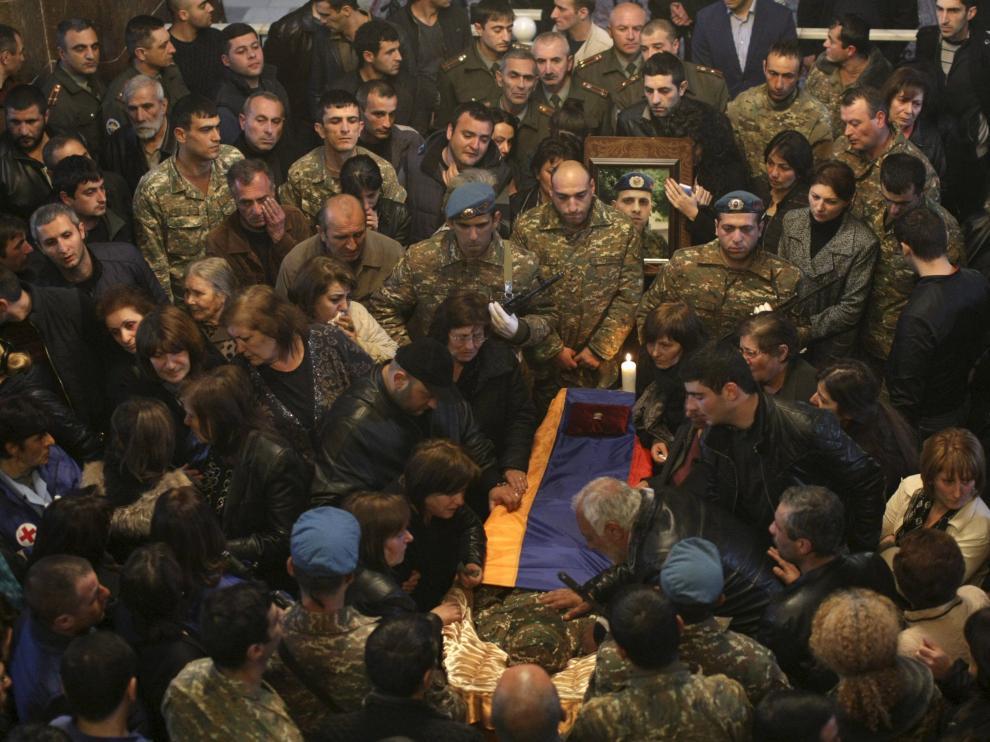 Decenas de personas rodean el féretro de un soldado armenio muerto.