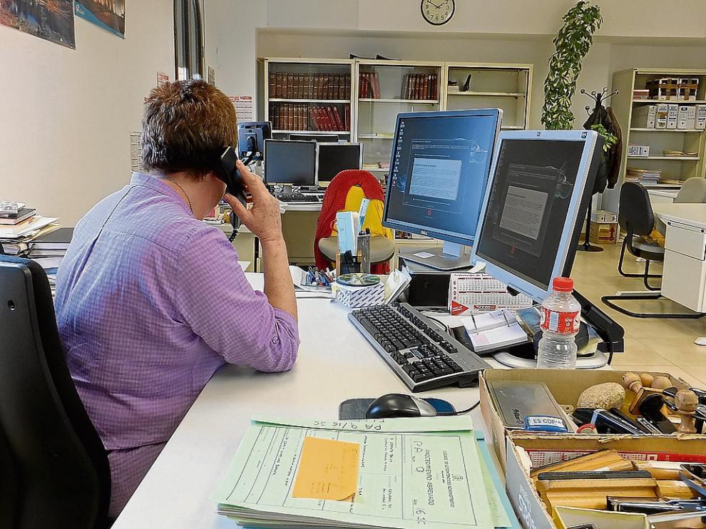 Una funcionaria atiende el teléfono ante dos ordenadores bloqueados por el virus.