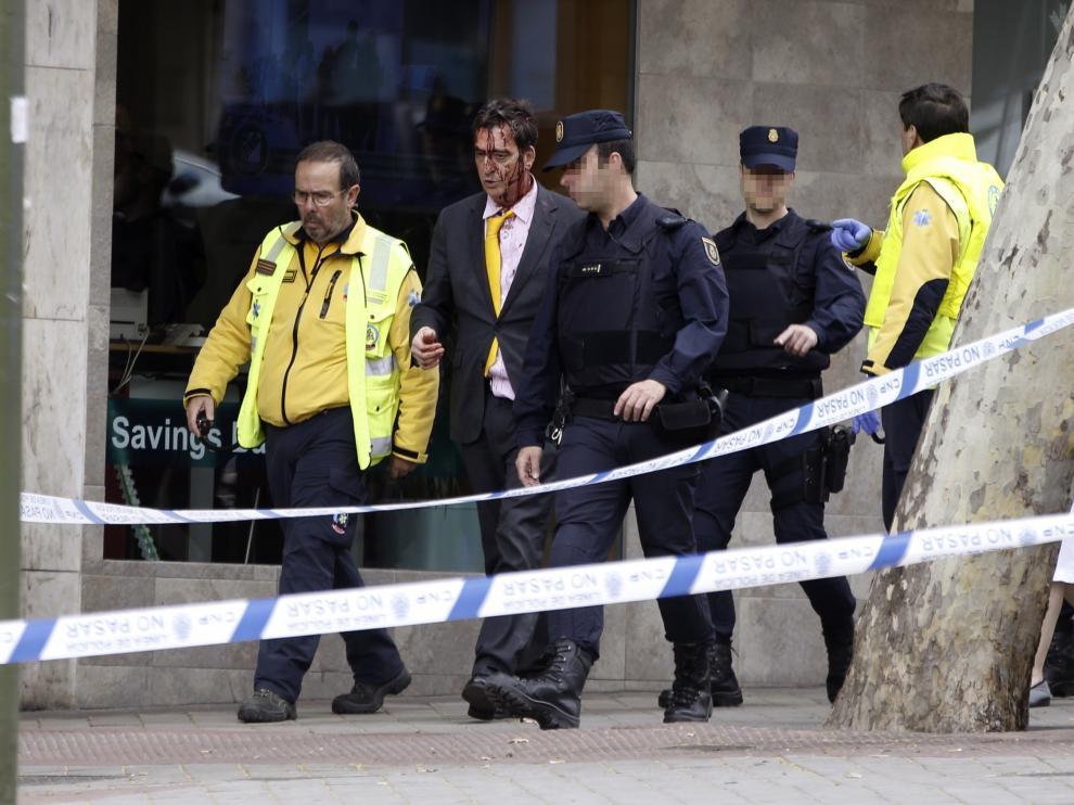 Policía y miembros del Samur acompañan al hombre herido tras sorprender a dos ladrones robando en una vivienda de Madrid.