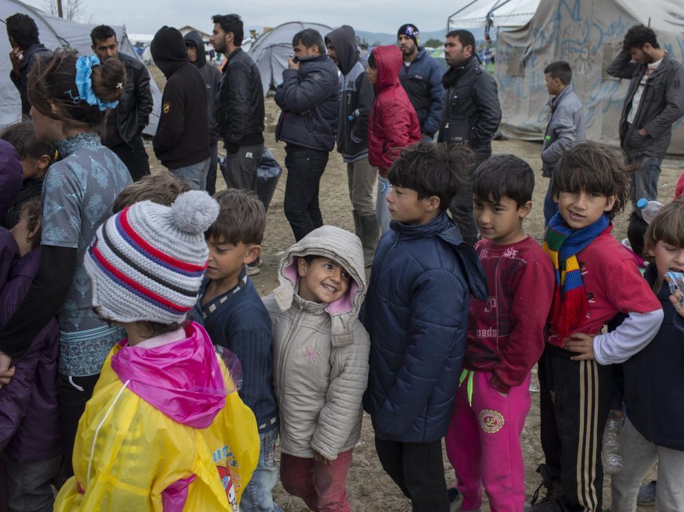 Niños refugiados hacen fila en el campo de Idomeni (Grecia) para obtener comida.