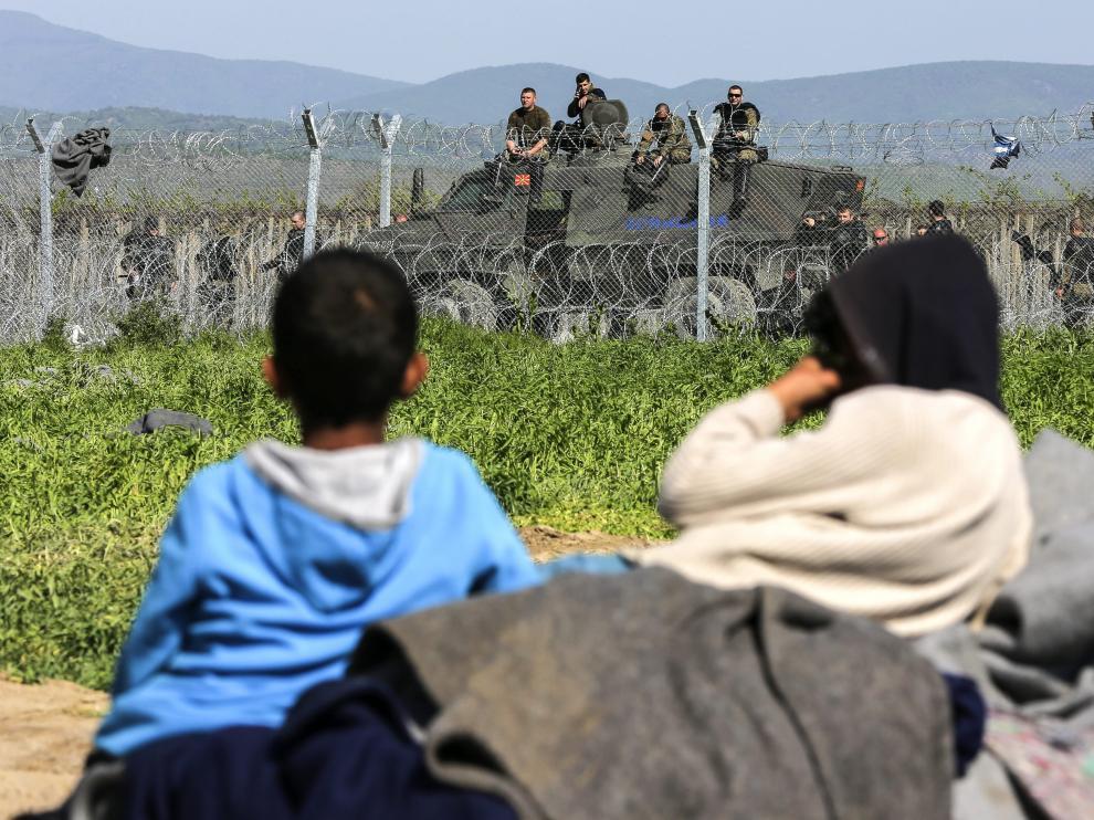 Unos niños descansan junto a la valla fronteriza en un campo de refugiados.