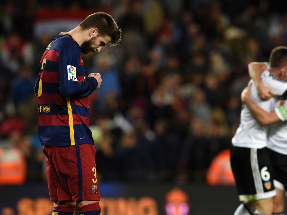El defensa, Gerard Piqué, se lamenta mientras los jugadores del Valencia celebran la victoria.