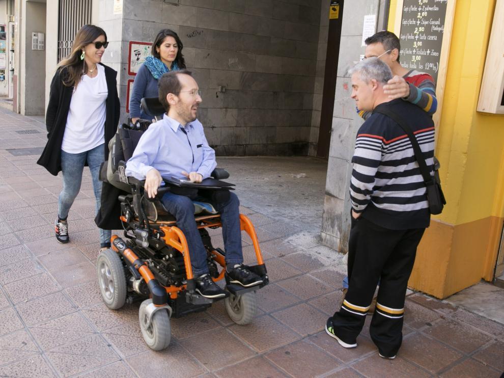 El secretario de Organización de Podemos, Pablo Echenique, saluda a unos ciudadanos en su camino hacia la rueda de prensa