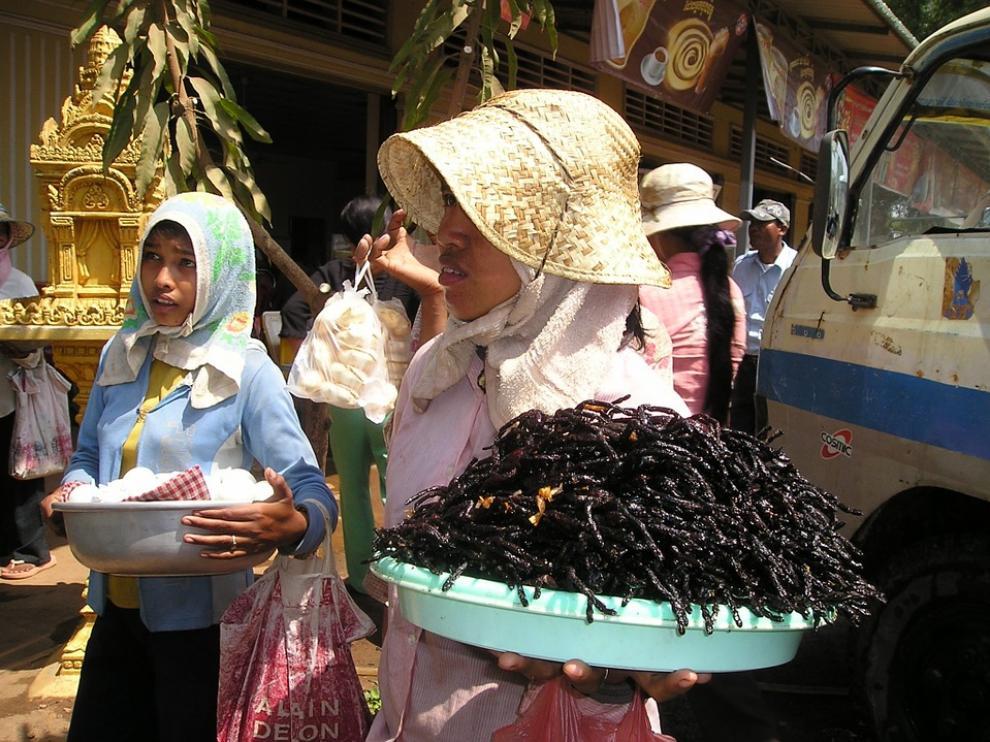 Una mujer camboyana sostiene un plato de tarántulas fritas.