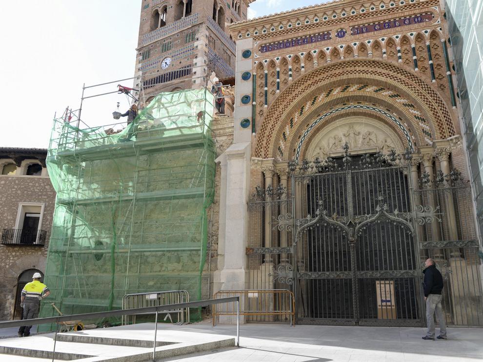 La verja del pórtico de la catedral, en medio de los andamios de las fachadas.