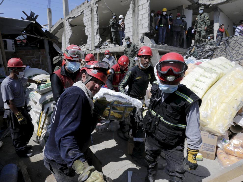 Miembros de los equipos de rescate trasladan a una víctima rescatada entre los escombros en Pedernales, Ecuador.
