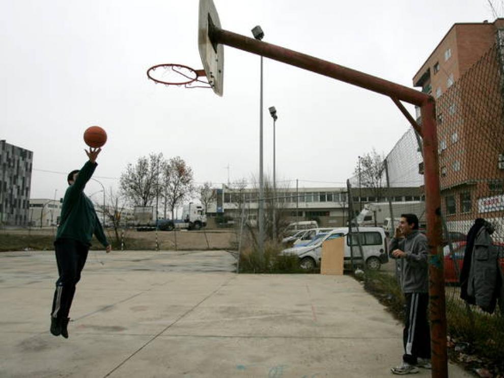 Dos jóvenes juegan a baloncesto en un potrero de Zaragoza