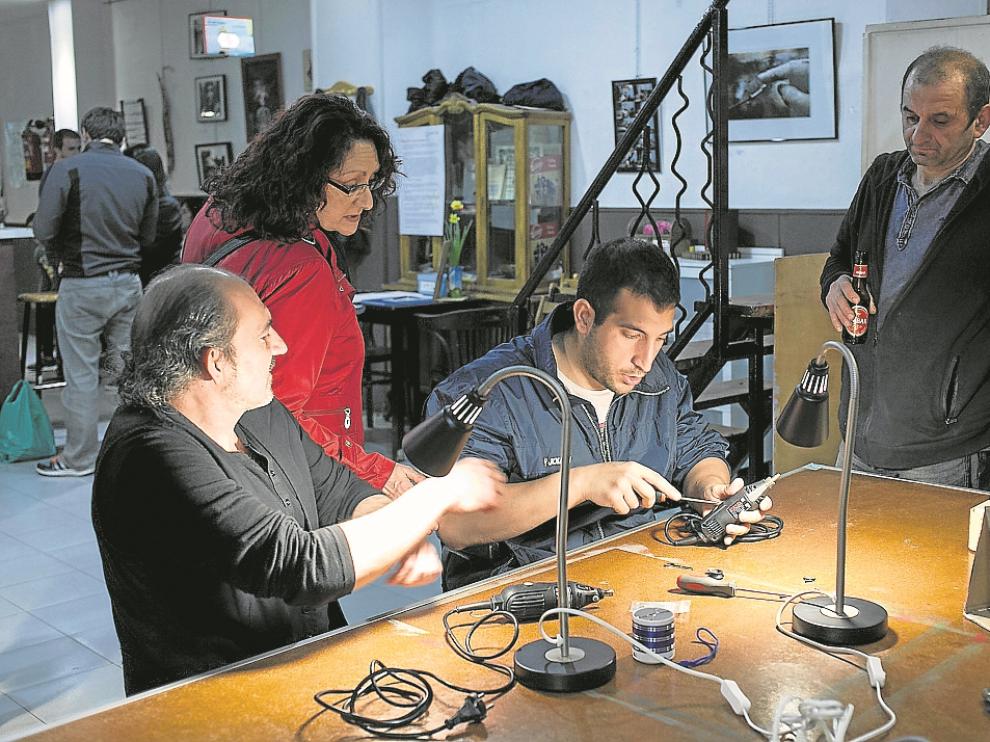 Luis Martín (centro), en pleno arreglo en el Repair Café de La Vía Láctea, en Zaragoza.