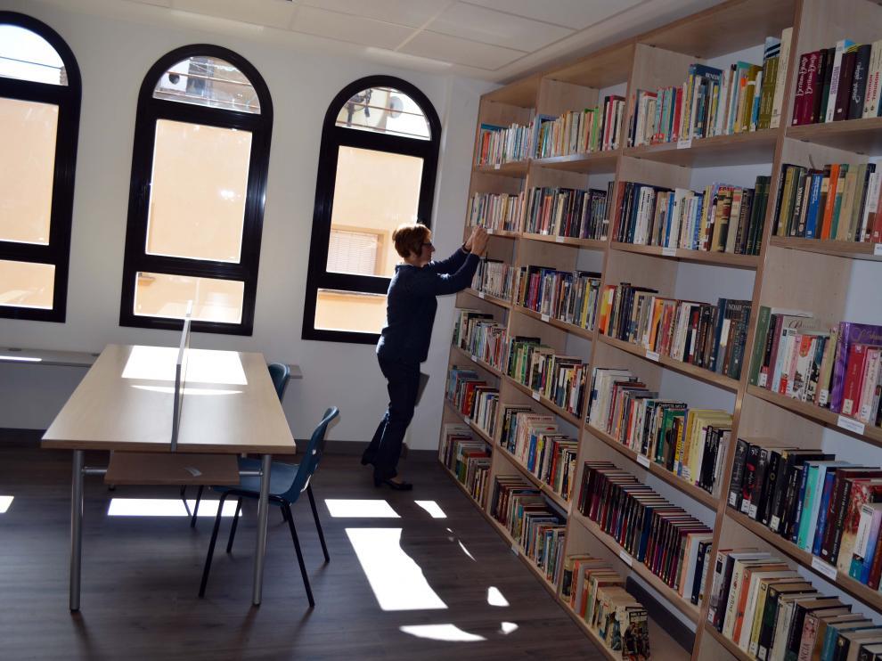 Una voluntaria coloca los libros de la nueva biblioteca.