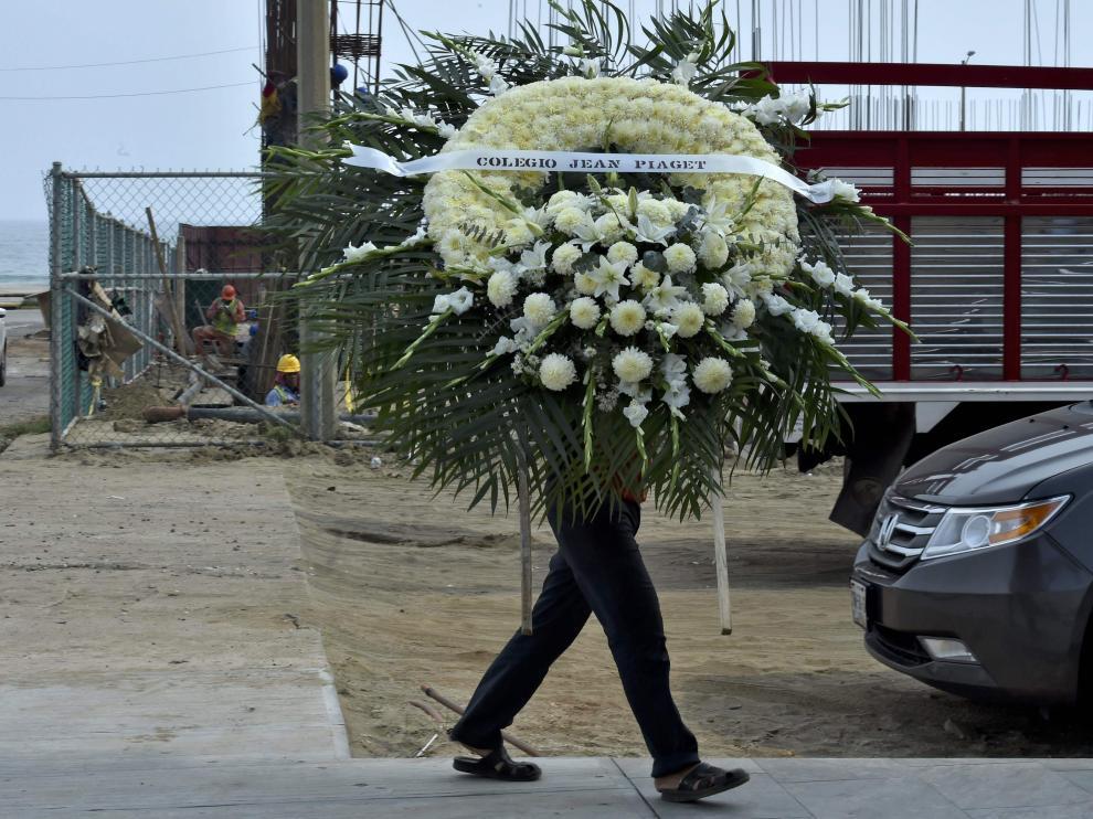 Un hombre sostiene un arreglo floral para uno de los fallecidos de la pasada explosión en México