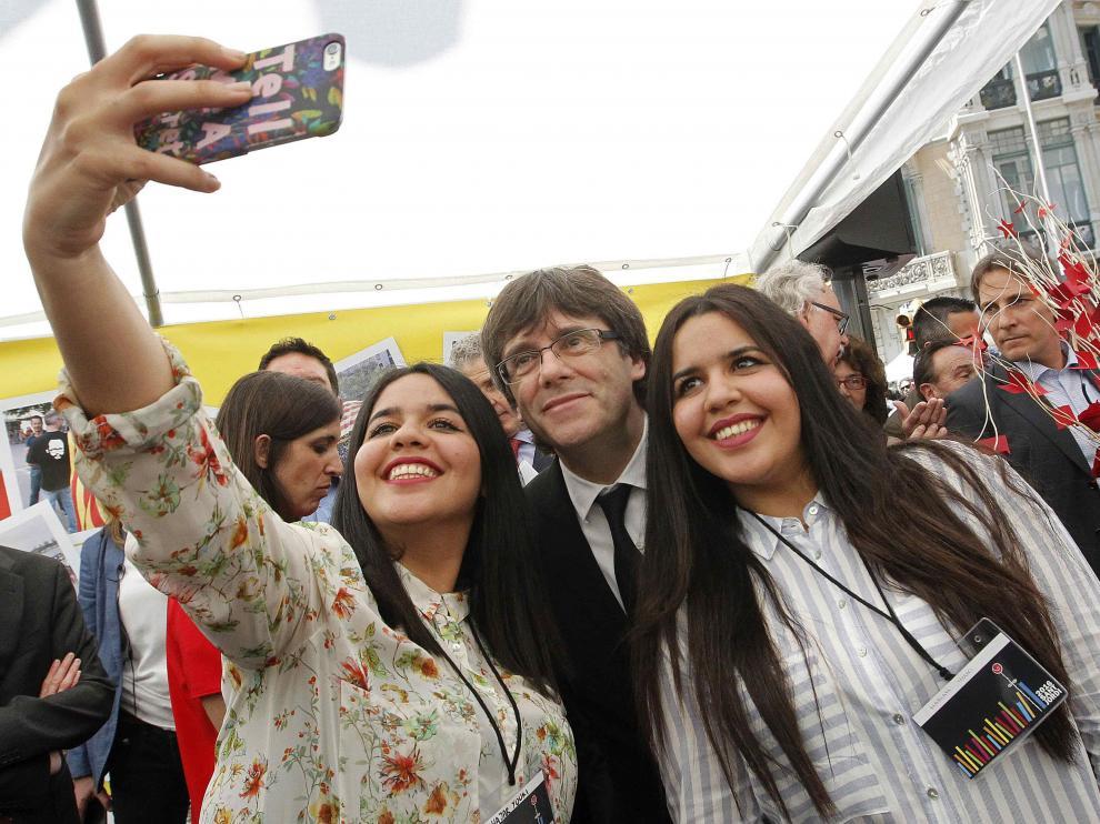 El president de la Generalitat, Carles Puigdemont, se hace una selfie con dos jóvenes en la caseta de la Asamblea Nacional Catalana
