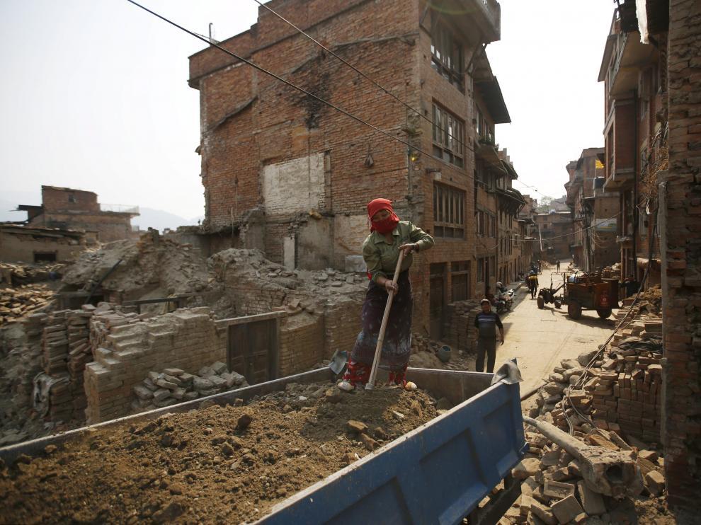 Una mujere trabaja en la reconstrucción de una vivienda en Nepal, un año después del terremoto.