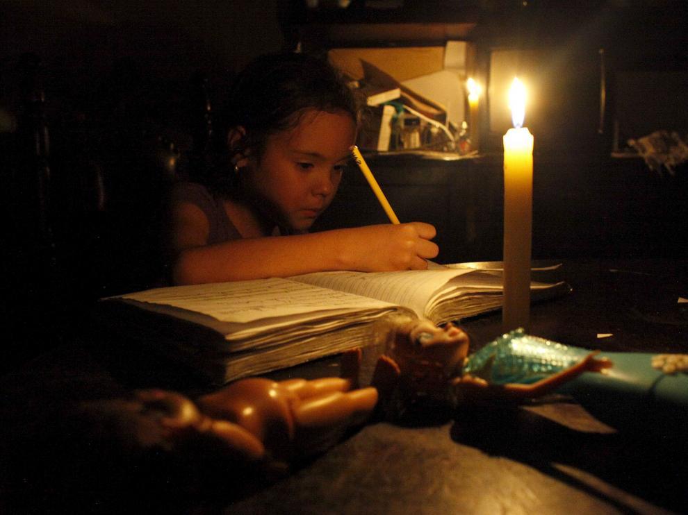 Una niña hace sus deberes con una vela encendida a causa de un corte de electricidad en San Cristóbal, en el estado de Tachira.