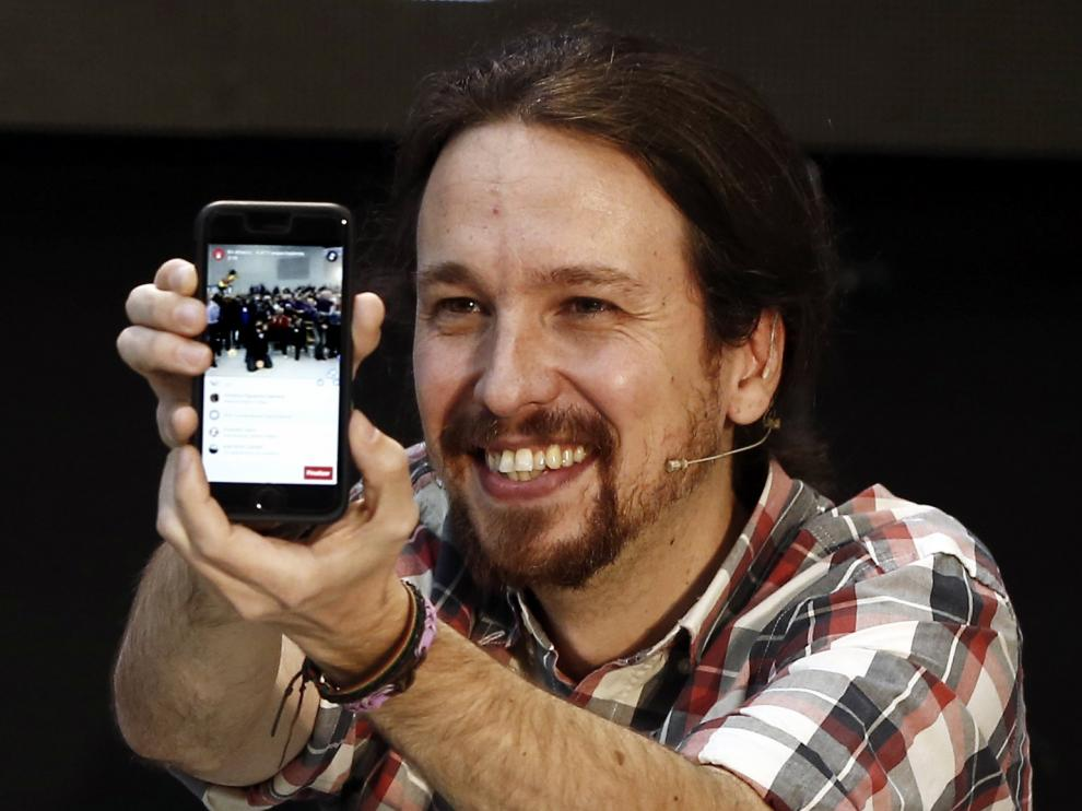 Pablo Iglesias (Podemos) muestra su móvil en un acto público.