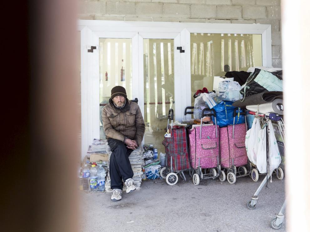 Eloy, sentando sobre una pila de periódicos. El 'guardián' del quiosco abandonado vive entre carros de la compra .
