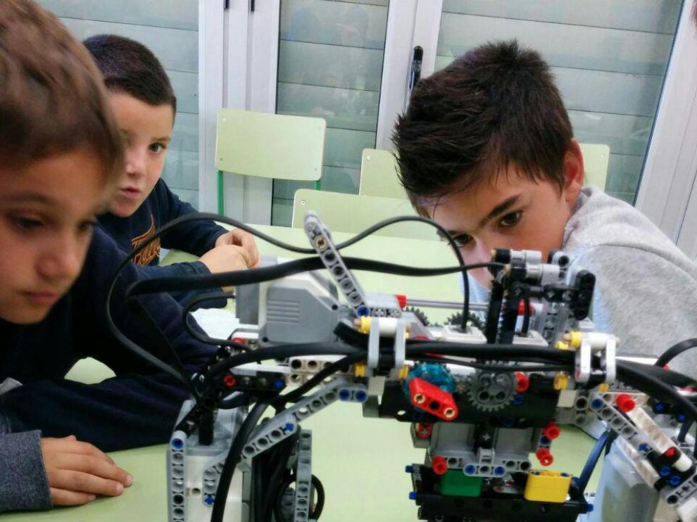 Unos niños disfrutan del taller de robótica en Huesca.