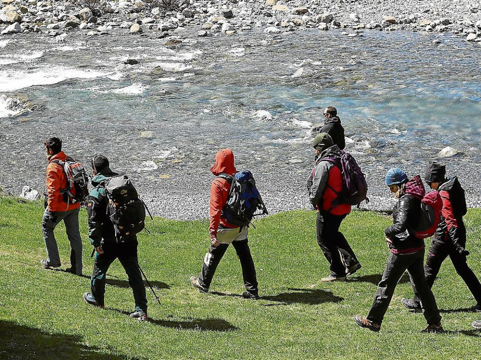 Un grupo de voluntarios, guiados por un forestal, inicia la búsqueda por las orillas del río.