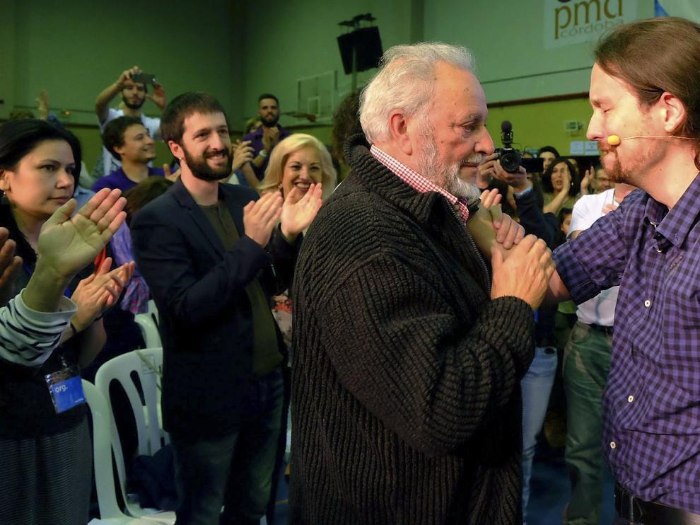 El secretario general de Podemos, Pablo Iglesias (d), se saluda con el exdirigente de IU, Julio Anguita