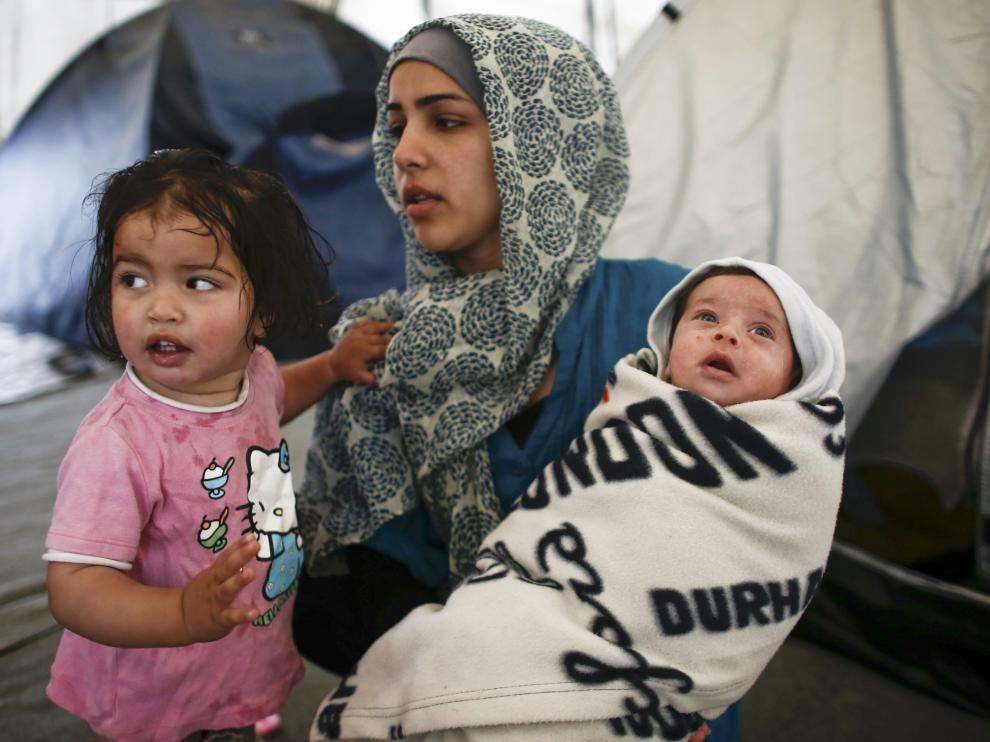 Una madre sostiene a sus dos hijos en el campo de refugiados de Idomeni.