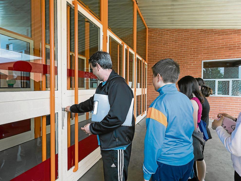 El profesor de educación física del Guillermo Fatás abre la puerta del pabellón a sus alumnos.