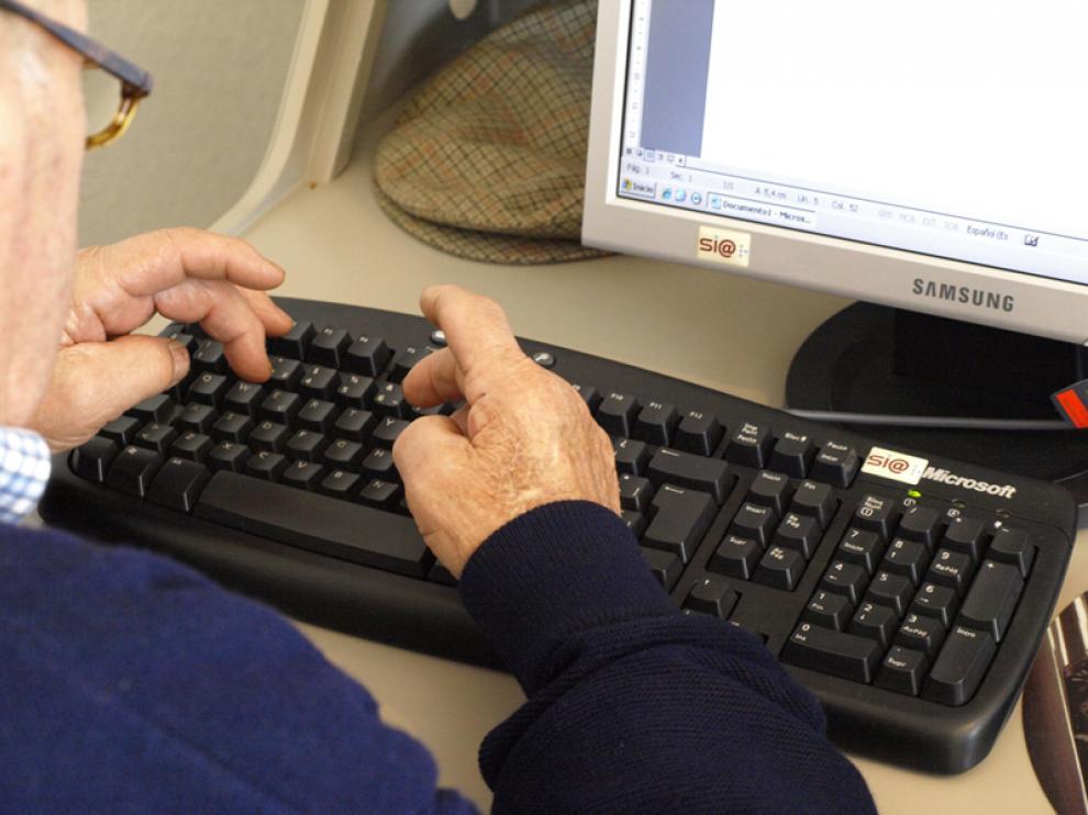 Un hombre mayor utiliza un ordenador.