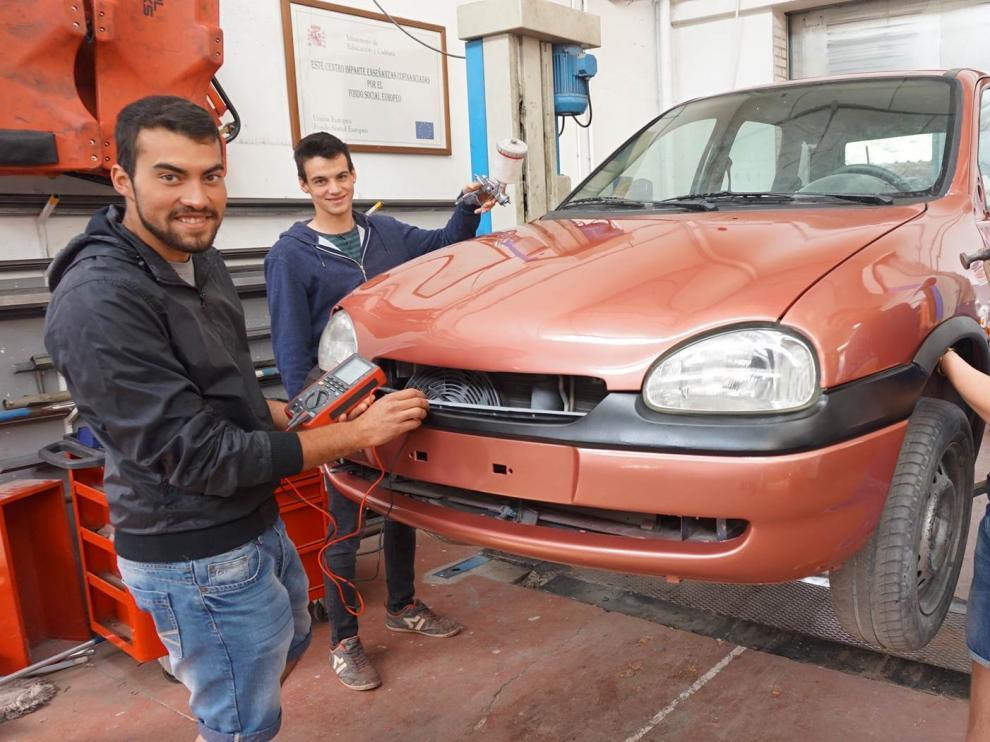 En la foto, los tres alumnos de automoción del IES Martínez Vargas arreglando un coche en el taller del centro.