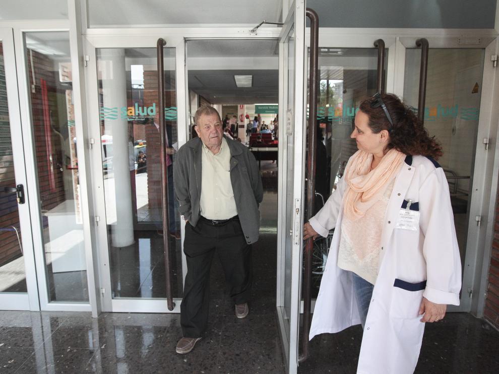 Una voluntaria abre la puerta del área de consultas externas del Obispo Polanco a un paciente.