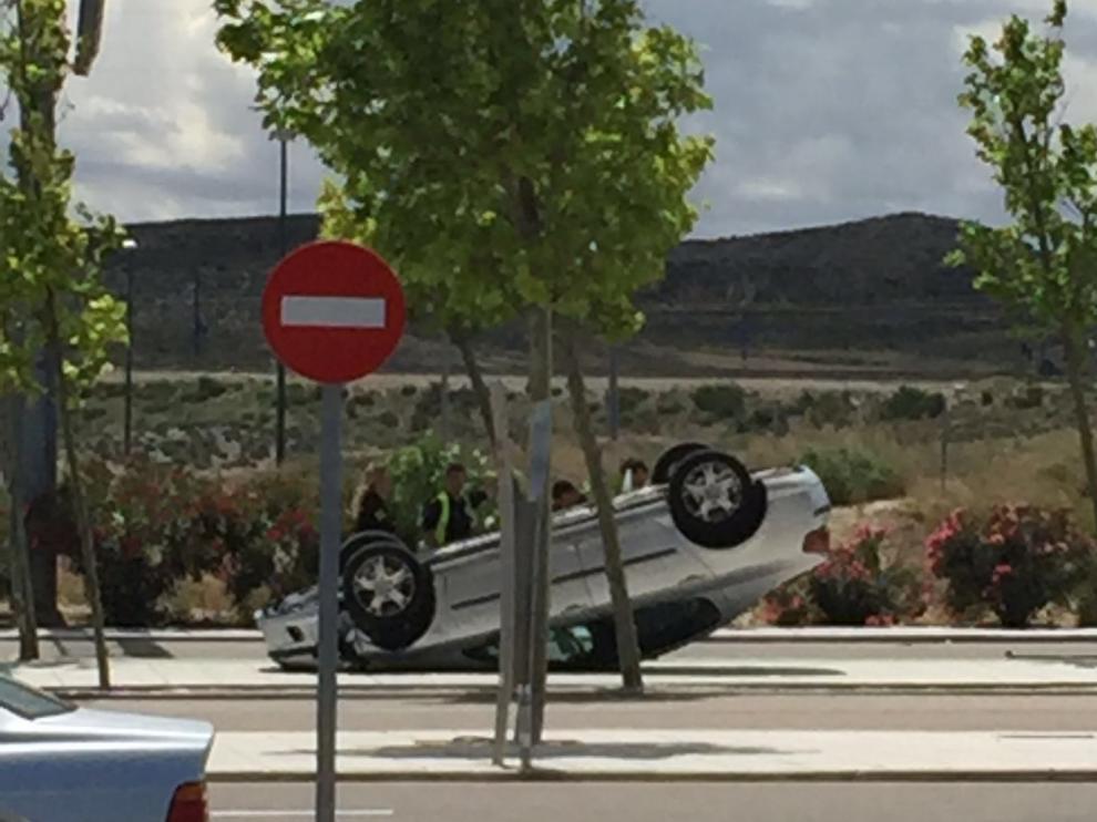El coche que ha volcado este lunes en el parking de Puerto Venecia.