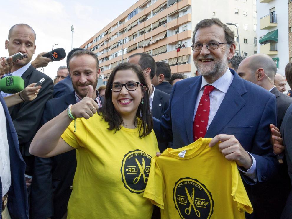 El presidente del Gobierno en funciones y candidato del PP a la reelección, Mariano Rajoy (d), con una simpatizante que lleva una camiseta de 'No a los recortes Religión'
