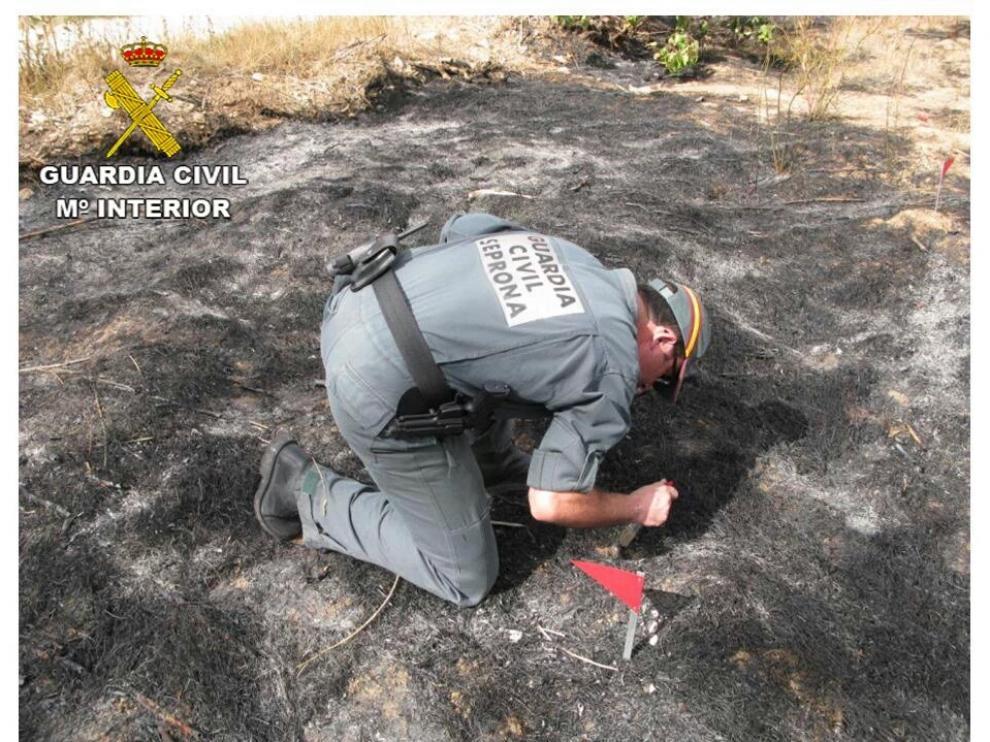 Un agente inspecciona el lugar en el que se produjo el incendio