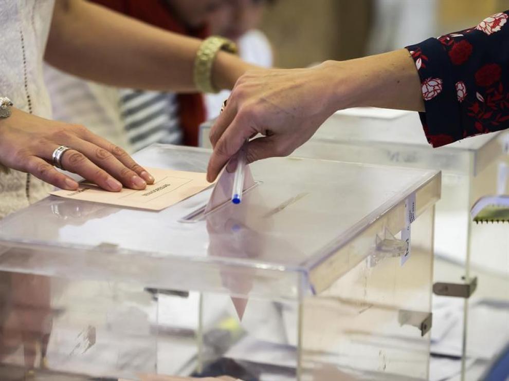 Foto de archivo de una mujer depositando su voto en una urna