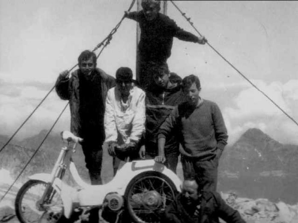Los seis amigos posan tras la moto y delante de la figura de la Virgen del Pilar que corona el Aneto