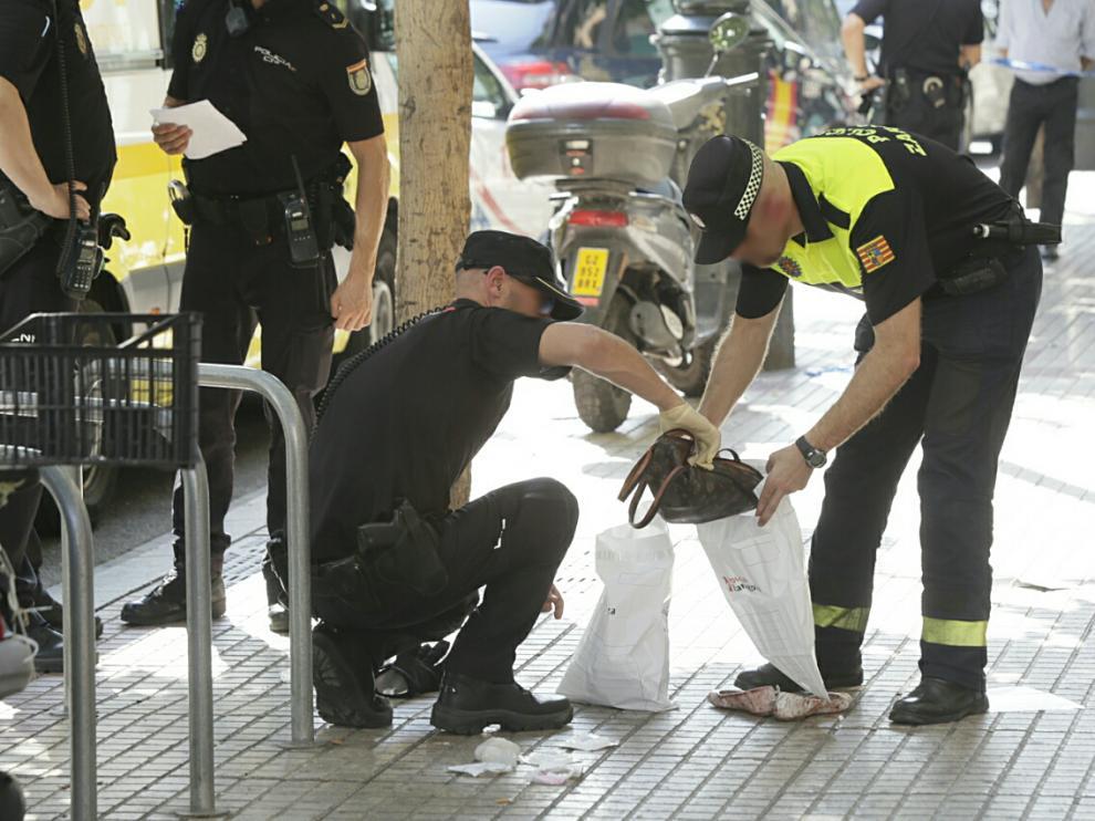 Dos agentes recogen el bolso de la víctima en el lugar de los hechos
