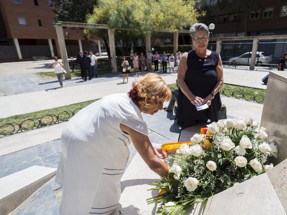 Marta Berdor, de blanco, y María Gracia Roca, colocan flores en el monumento de la casa cuartel.