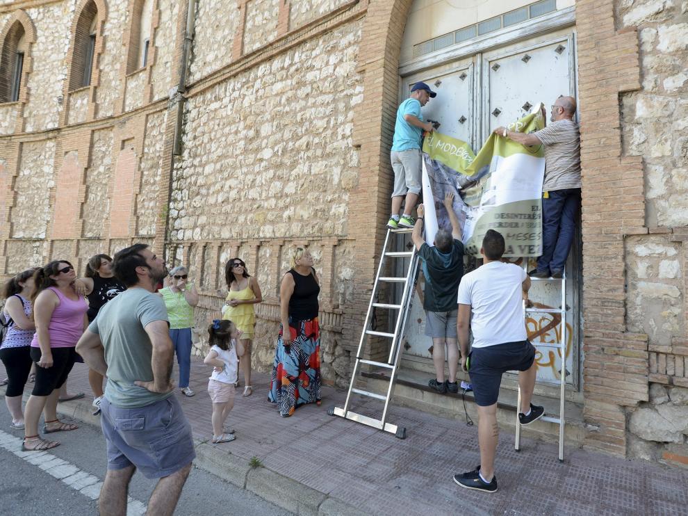 Un grupo de vecinos cuelga el cartel en la fachada del antiguo asilo de San José.