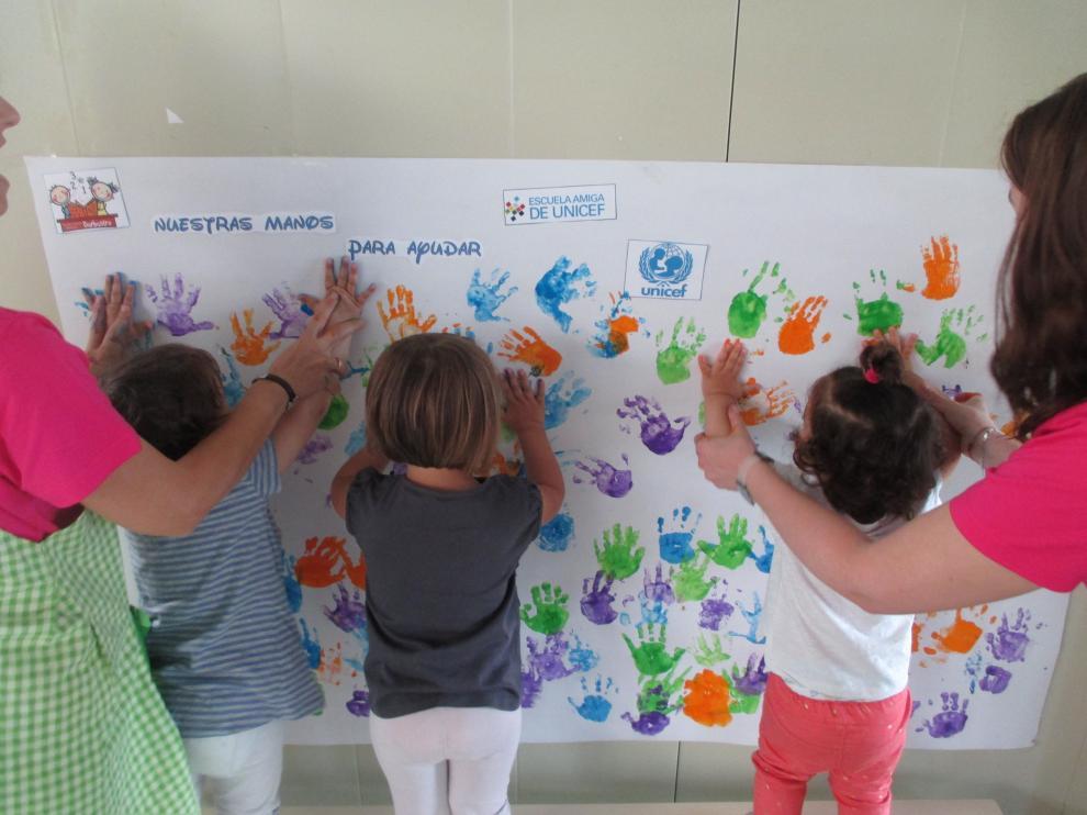 Alumnos de Infantil de la escuela de Barbastro plasman sus manos sobre el mural.