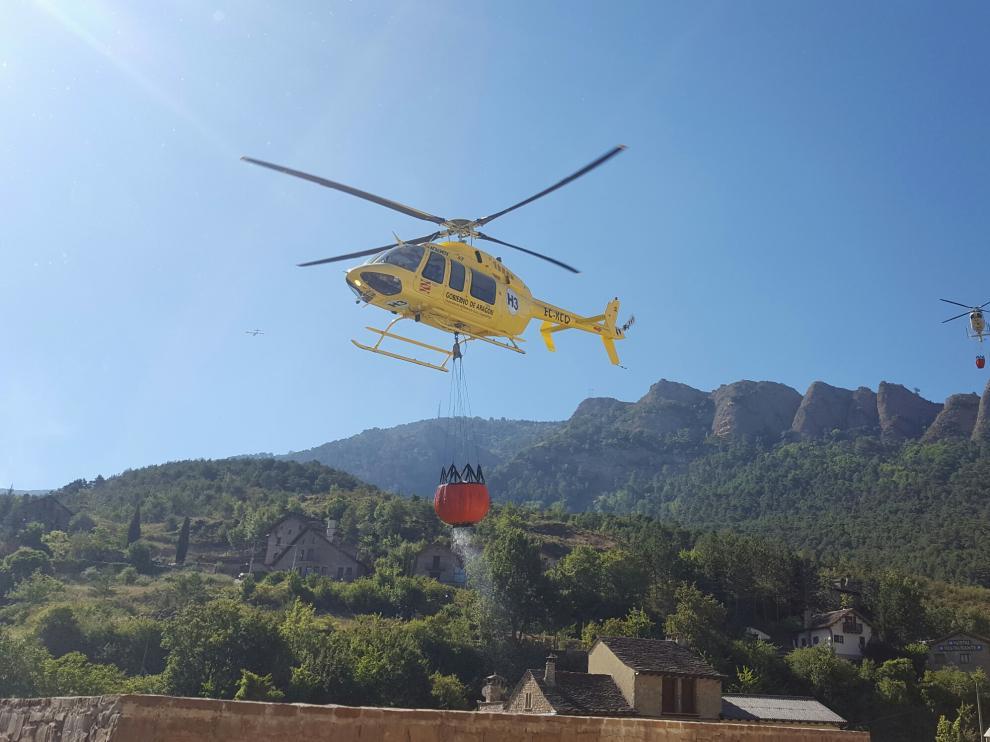 Un helicóptero carga agua antes de dirigirse hacia el incendio