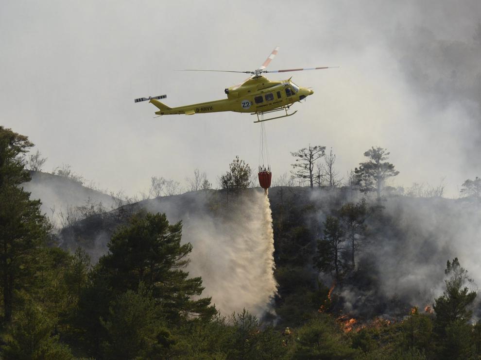 Un helicóptero suelta agua para sofocar el fuego que había llegado a los barrancos en Atarés .