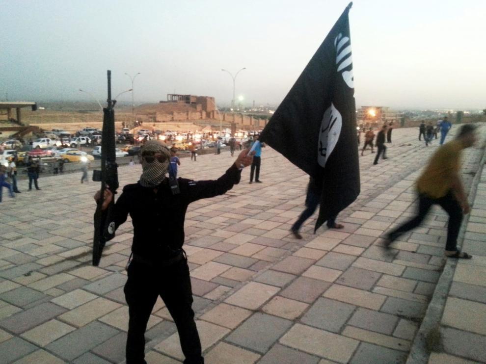 Un combatiente del Estado Islámico sostiene un arma y una bandera en la ciudad iraquí de Mosul.
