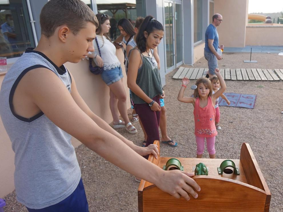 Una niña lanza la ficha en el popular juego de la rana, una de las actividades más practicadas.